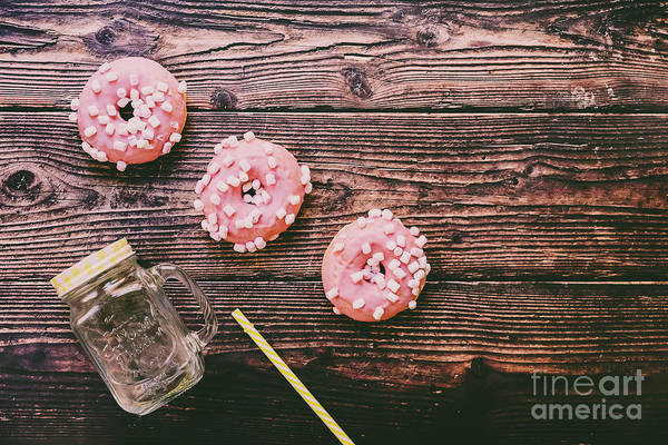 Wall Art - Photograph - Jug Of Juice With Colorful Straw And Pink Glazed Donuts On Woode by Joaquin Corbalan