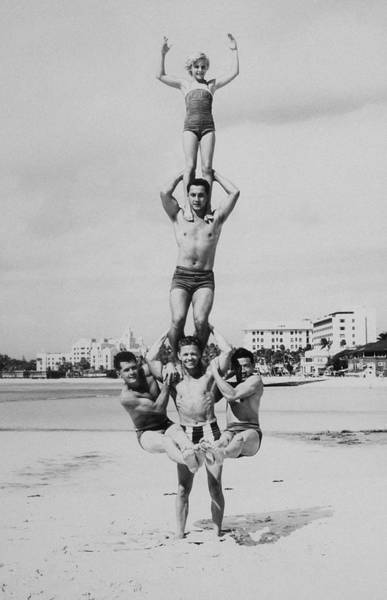 Acrobat Wall Art - Photograph - Men And Girl Perform Acrobatics On Beach by Archive Holdings Inc.