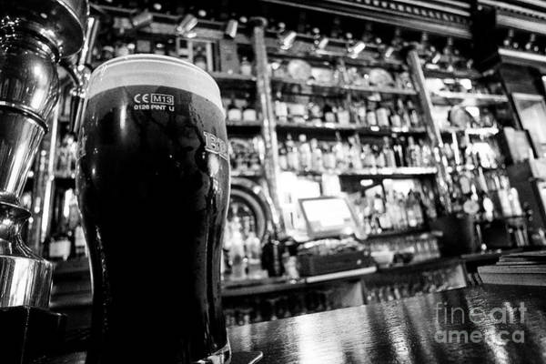 Wall Art - Photograph - pint of beamish stout in The Long Hall victorian pub one of the oldest pubs in Dublin republic of Ir by Joe Fox