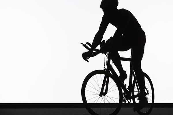 Helmet Photograph - Silhouette Of Triathlete Riding On by Paul Taylor