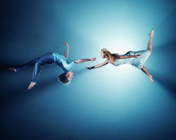 Heterosexual Couple Photograph - Young Couple In Air, Low Angle View by Henrik Sorensen
