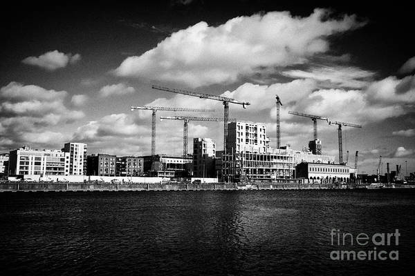 Wall Art - Photograph - cranes and new office developments at north dock in the docklands waterfront river liffey Dublin Rep by Joe Fox