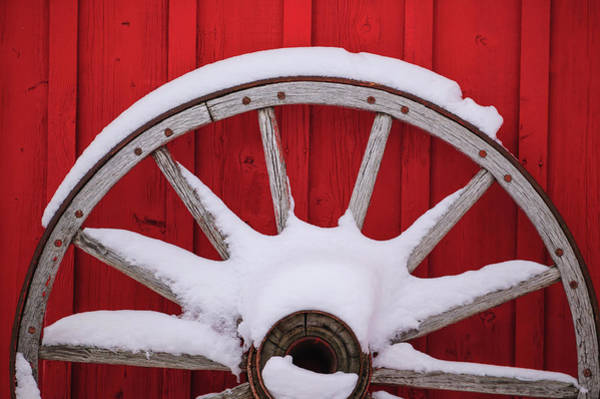Wall Art - Photograph - Snow-covered Wagon Wheels Against Red by Stuart Westmorland