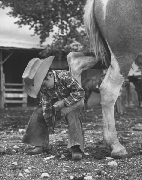 Learning Photograph - 6 Yr. Old Cowboy Learning How To Shoe A by Allan Grant