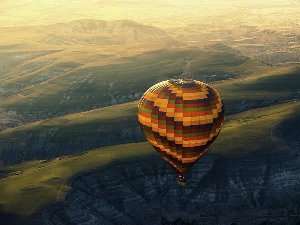 Cappadocia Photograph - A Balloon Fly Over Cappadocia Landscape by Coolbiere Photograph