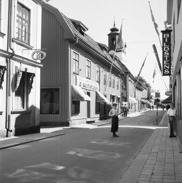 Wall Art - Painting - A Boy Standing In Norra Storgatan  North High Street  With Shops. In The Background The Tower Of Ek by Celestial Images