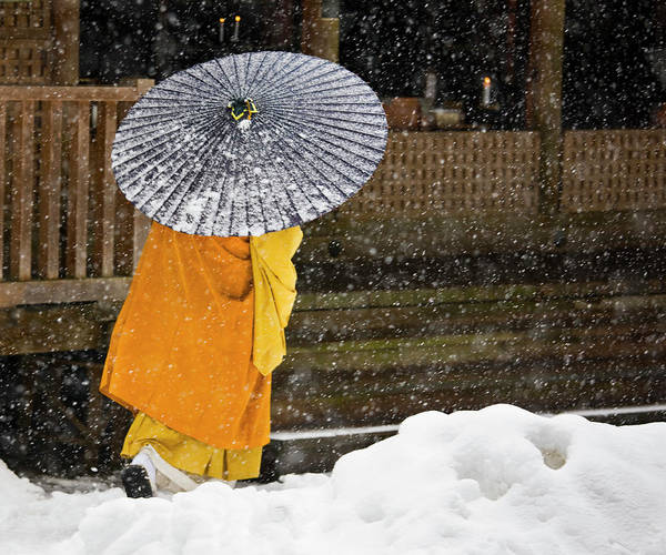 Thoroughfare Photograph - A Buddhist Monk Walks Through A Snow by Mint Images - Art Wolfe