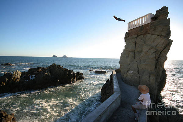 Waters Edge Wall Art - Photograph - A Cliff Diver Plunges Into The Pacific by Robcocquyt