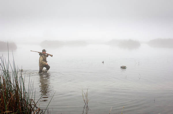 Rifle Photograph - A Hunter In The Water Wearing by Laura Ciapponi / Design Pics