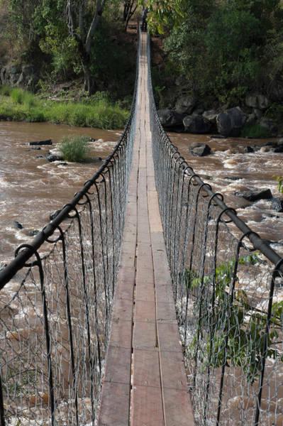 Hanging Rock Photograph - A Long Suspension Bridge Over A River by Diane Levit / Design Pics