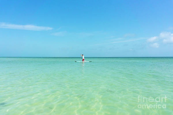 Photograph - A Man Rides A Paddleboard In The Shallow Waters Near The City Pi by William Kuta