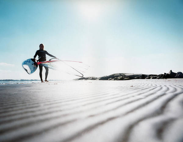 Windsurfing Photograph - A Person Standing On A Beach Holding A by Oscar Mattsson