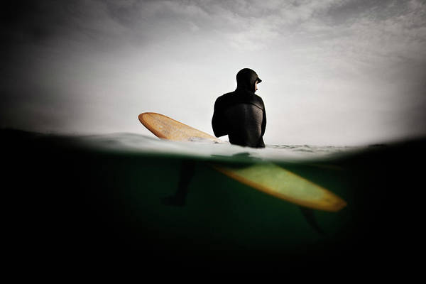 Water Sport Photograph - A Surfer On A Surfboard Looking Over by Mint Images - Jonathan Kozowyk