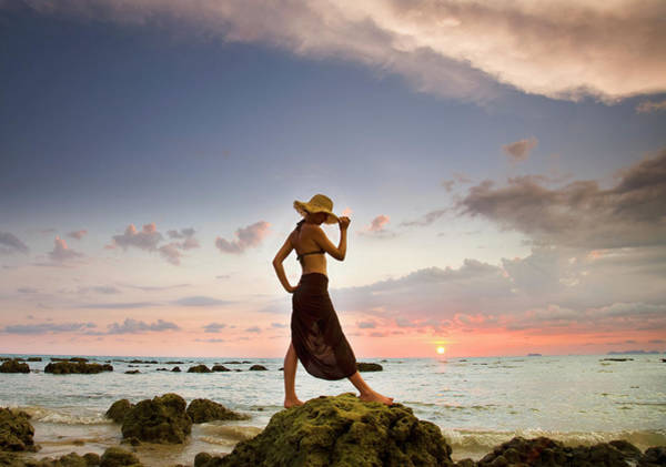 Bikini Photograph - A Woman Wearing A Hat And Sarong Stands by Sean White / Design Pics