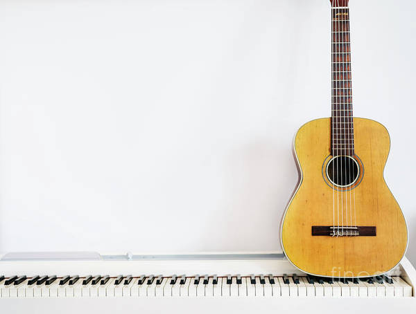 Wall Art - Photograph - Acoustic Guitar On Piano Keyboard In Front Of White Wall. by Jelena Jovanovic