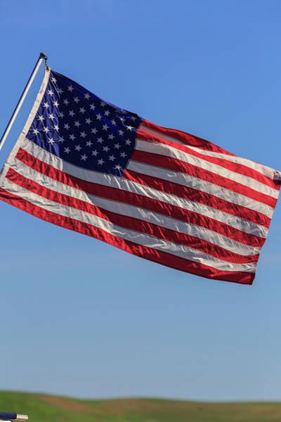 Stuart Photograph - American Flag Flying Against A Blue Sky by Stuart Westmorland