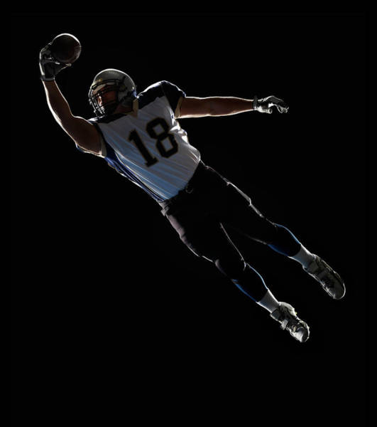Football Helmet Photograph - American Football Player Leaping To by Lewis Mulatero