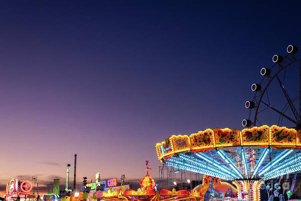 Photograph - Amusement Park At Dusk With Ferris Wheel In The Background. by Joaquin Corbalan