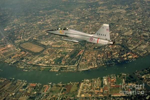 Photograph - An American-made Thai Air Force Jet Sweeps Over Bangkok. by Dean Conger