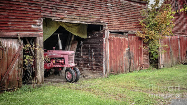 Photograph - Antique Farmall Tractor Poking Out Of The Old Barn by Edward Fielding
