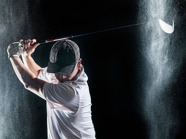Rain Photograph - Asian Golf Player Swinging Club In Rain by Erik Isakson