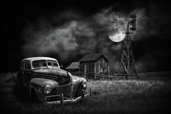 Photograph - Automobile And Wooden Barn With Windmill By Moon Light In Black And White by Randall Nyhof