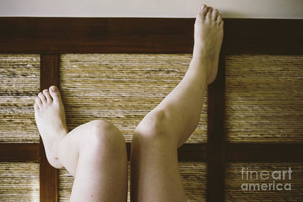 Photograph - Bare Feet Of Woman Leaning On The Headboard Of Her Bed In A Sexy Way. by Joaquin Corbalan