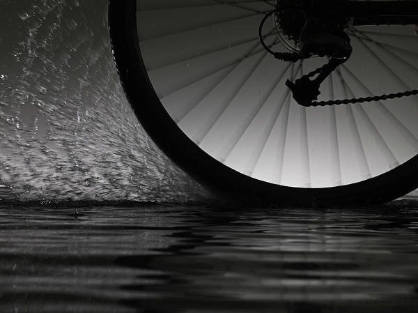 On The Move Photograph - Bike Riding  Through Water by Jonathan Knowles