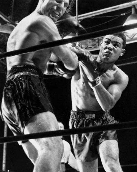 Boxing Photograph - Boxer Joe Louis Lands Punch On Lou Nova by New York Daily News Archive
