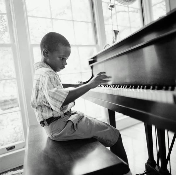 Piano Photograph - Boy 6-8 Playing Piano In Home B&w by Tony Anderson