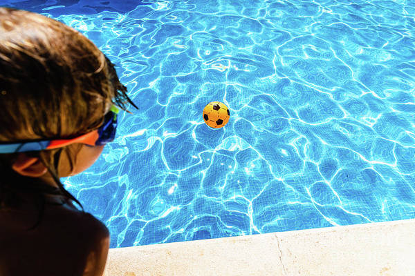 Photograph - Boy Observing A Ball Moving Away From Him In A Pool In Summer, C by Joaquin Corbalan