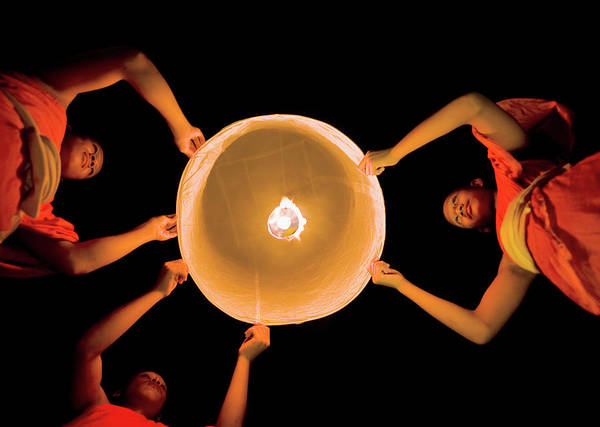 Shaved Head Photograph - Buddhist Monks Launching A Khom Loy by Martin Puddy