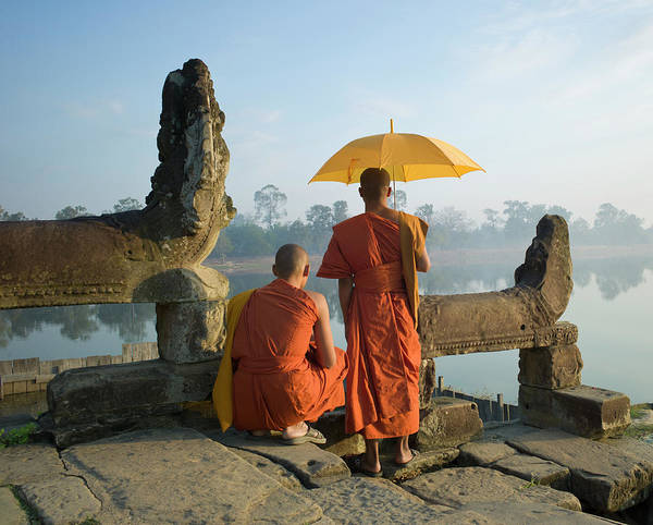 Reap Photograph - Buddhist Monks Standing Next To Stone by Martin Puddy