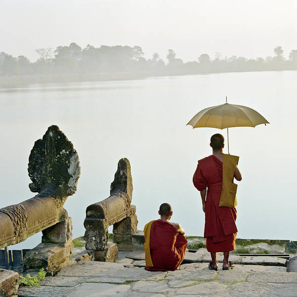 Reap Photograph - Buddhist Monks Standing On Waters Edge by Martin Puddy