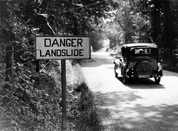 Danger Photograph - Car Passing Danger Landslide Sign  B&w by Hulton Archive