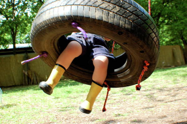 Wall Art - Photograph - Child In Boots Swinging On A Tire Swing by Meredith Winn Photography