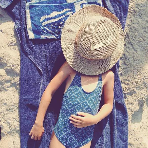 Sun Hat Photograph - Child In Swimsuit Laying On Towel With by Jodie Griggs