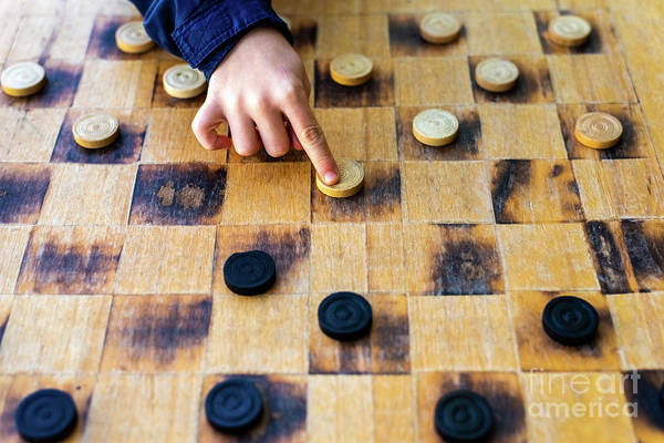 Photograph - Child's Hands Moving Pieces Of Checkers Game, Concepts Of Struggle, Strategy And Confrontation. by Joaquin Corbalan