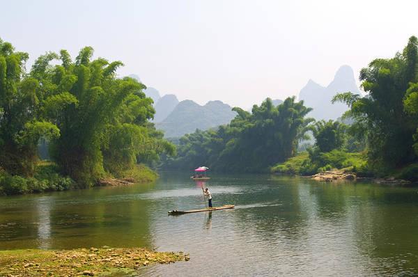 Raft Photograph - Chinese Man In Bamboo Raft At Yulong by Nancy Brown