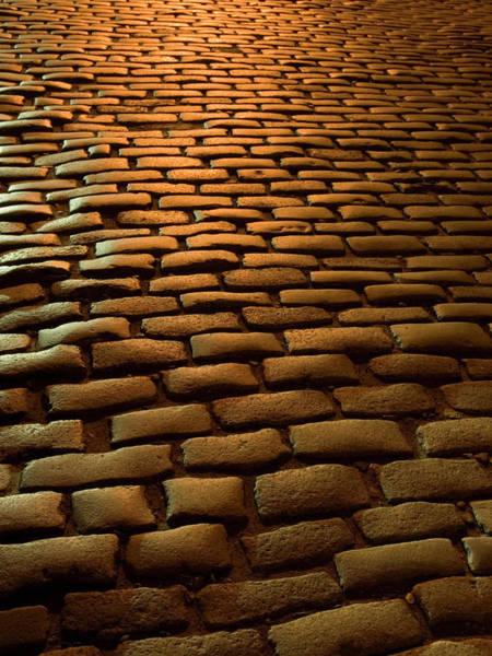 Photograph - Close-up Of Cobblestone Street At Night by Jeff Spielman
