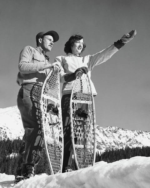 Heterosexual Couple Photograph - Couple Holding Snowshoes, Woman Pointing by Stockbyte