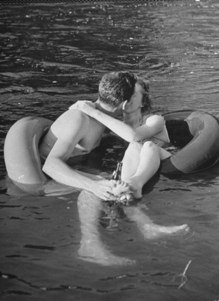Vertical Photograph - Couple Kissing While Innertube Floating by Alfred Eisenstaedt