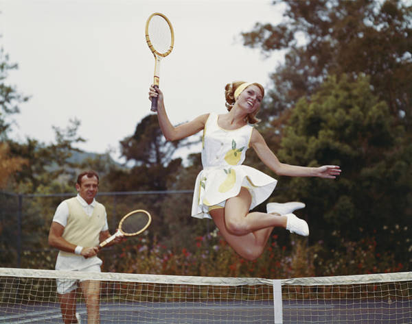 Toothy Smile Photograph - Couple On Tennis Court, Woman Jumping by Tom Kelley Archive