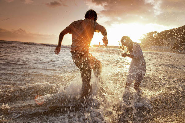 Heterosexual Couple Photograph - Couple Playing In Waves At Beach by Walter Zerla