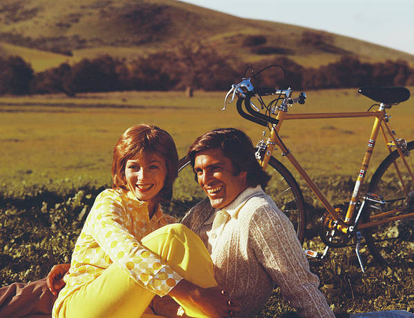 Heterosexual Couple Photograph - Couple Sitting In Field With Bicycle by Tom Kelley Archive