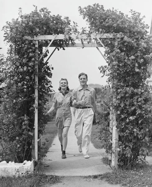 Heterosexual Couple Photograph - Couple Walking On Footpath Towards Rose by George Marks
