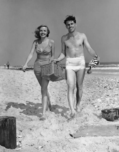 Heterosexual Couple Photograph - Couple Walking With Picnic Basket On by George Marks