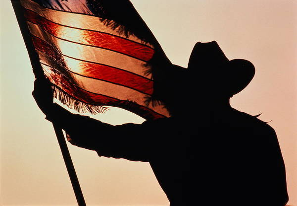 Cowboy Hat Photograph - Cowboy Holding Stars And Stripes by Donovan Reese