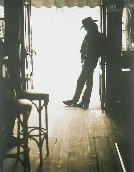 Toughness Photograph - Cowboy Leaning In Doorway by John Halpern