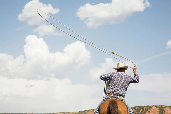 Wall Art - Photograph - Cowboy On Horseback Swinging Lasso by Andrew Geiger